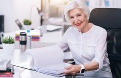 Очаровывая постаретая дама дела работая в офисе стоковое изображение