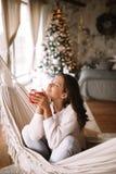 Очаровывая темн-с волосами девушка одетая в бежевых свитере и брюках держит красную чашку сидя в гамаке в уютном украшенный стоковые изображения