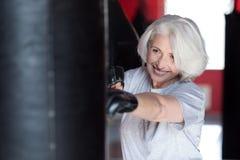 Очаровывая усмехаясь активная груша бокса женщины Стоковая Фотография RF