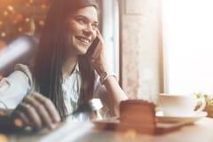 Очаровывая усмехаясь женщина говоря на телефоне в кафе Вкусные шоколадный торт и кофе на таблице Яркое солнечное утро в кафе Стоковое Фото