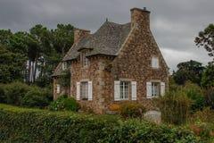 Очаровывая фантастический средневековый загородный дом в сельской местности с высокой крышей и окнами с белыми шторками с зеленым стоковое фото rf