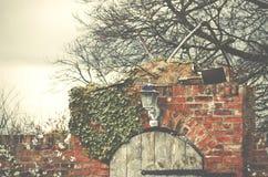 Очаруйте стену деревянной двери и красных кирпичей к месту фермы в Yorks Стоковое Фото