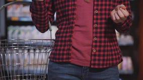Очень близкий взгляд женщины которая идет в супермаркет с пустой корзиной акции видеоматериалы