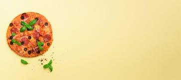 Очень вкусная итальянская пицца, базилик выходит, солит, перчит на желтой предпосылке с copyspace Взгляд сверху знамена картина д стоковая фотография rf