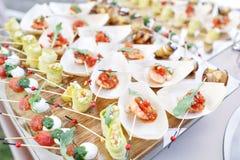 Очень вкусная креветка и отрезанные томаты на деревянной шлюпке Цукини свертывает с гайками сосны Вкусная таблица шведского стола стоковая фотография rf