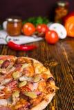 Очень вкусная пицца на деревянном столе, томатах и других овощах i стоковое изображение rf