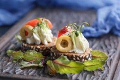 Очень вкусное канапе с семгами, творогом, оливкой с микро- зелеными цветами на темной предпосылке Холодная закуска Стоковое Фото