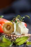 Очень вкусное канапе с семгами, творогом, оливкой с микро- зелеными цветами на темной предпосылке Холодная закуска Стоковые Фотографии RF