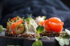 Очень вкусное канапе с семгами, творогом, оливкой с микро- зелеными цветами на темной предпосылке Холодная закуска Стоковое фото RF