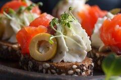 Очень вкусное канапе с семгами, творогом, оливкой с микро- зелеными цветами на темной предпосылке Холодная закуска Стоковые Фото
