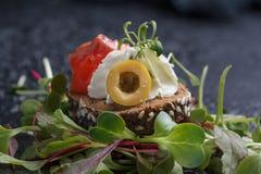 Очень вкусное канапе с семгами, творогом, оливкой с микро- зелеными цветами на темной предпосылке Холодная закуска Стоковая Фотография RF