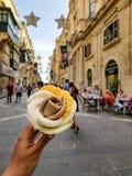 Очень вкусное розовое мороженое в руке девушки на улице Валлетты стоковая фотография rf