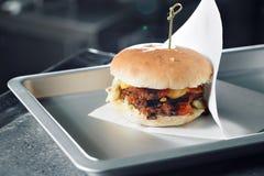 Очень вкусные бургеры с говядиной, томатом, сыром и салатом сваренный на собранном гриле Стоковые Изображения