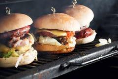 Очень вкусные бургеры с говядиной, томатом, сыром и салатом сваренный на собранном гриле нагрейте гриль и дым стоковые фото