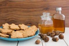 Очень вкусные канадские печенья сливк клена на голубой плите с медом, Стоковые Фото