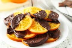 Очень вкусные куски апельсина покрыли шоколад на плите на белой деревянной предпосылке Стоковые Изображения RF