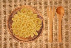 Очень вкусные макаронные изделия на деревянных плите, вилке и ложке на backgr мешковины Стоковые Изображения RF