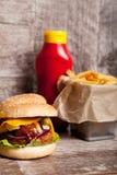 Очень вкусные домашние сделанные cheeseburgers на деревянной плите Стоковые Фото