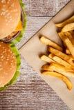 Очень вкусные домашние сделанные cheeseburgers на деревянной плите Стоковое Изображение