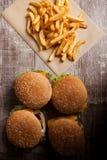 Очень вкусные домашние сделанные cheeseburgers на деревянной плите Стоковая Фотография RF