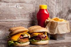 Очень вкусные домашние сделанные cheeseburgers на деревянной плите Стоковое Фото