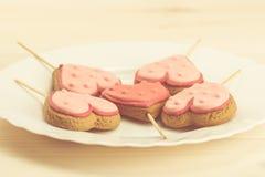 очень вкусные печенья на белой плите в форме сердца на деревянной предпосылке Стоковые Фотографии RF