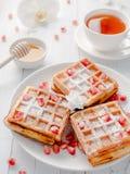 Очень вкусные рт-моча венские waffles с семенами меда и гранатового дерева на белой плите, светлой деревянной предпосылке Стоковая Фотография RF