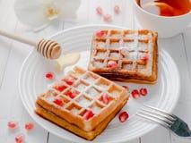 Очень вкусные рт-моча венские waffles с семенами меда и гранатового дерева на белой плите, светлой деревянной предпосылке Стоковое Фото