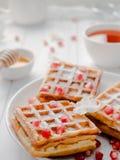 Очень вкусные рт-моча венские waffles с семенами меда и гранатового дерева на белой плите, светлой деревянной предпосылке Стоковые Изображения