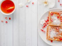 Очень вкусные рт-моча венские waffles с семенами меда и гранатового дерева на белом космосе экземпляра плиты Стоковое Изображение