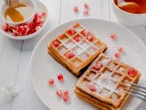 Очень вкусные рт-моча венские waffles с семенами меда и гранатового дерева на белой плите, светлой деревянной предпосылке Стоковые Фото