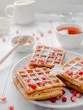 Очень вкусные рт-моча венские waffles с семенами меда и гранатового дерева на белой плите, светлой деревянной предпосылке Стоковое фото RF