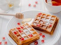 Очень вкусные рт-моча венские waffles с семенами меда и гранатового дерева на белой плите, светлой деревянной предпосылке Стоковые Изображения RF