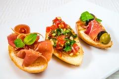Очень вкусные, рт-моча различные канапе с мясом, овощи, травы и оливки, на белой плите Горизонтальная рамка Стоковые Изображения