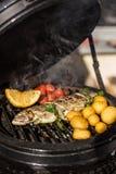 Очень вкусные рыбы радужной форели с томатами, картошками и лимоном варя на горячем пламенеющем гриле Барбекю Ресторан Стоковая Фотография