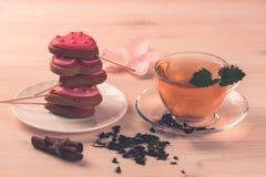 Очень вкусные свежие печенья в форме сердца на белой плите на деревянной предпосылке чай чашки зеленый Стоковое Изображение