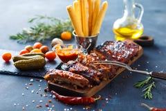 Очень вкусные barbecued нервюры закалённые с пряным наметывая соусом и, который служат с прерванный Стоковые Фотографии RF