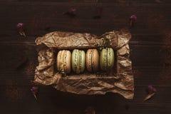 Очень вкусные macaroons в подарочной коробке на деревянном столе, взгляд сверху Стоковое Фото