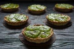 Очень вкусные tartlets заполнили с сливк и покрыли с кусками кивиа стоковое фото