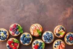 Очень вкусные tartlets или торт ягоды с коркой и мятой лимона плавленого сыра украшенными листают сверху Вкусные десерты печенья Стоковое фото RF