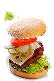 Очень вкусный бургер с ингридиентами летания падая на белой предпосылке Стоковое Изображение