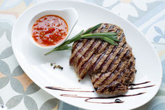 Очень вкусный зажаренный стейк с соусом и специями на белой плите Стоковое Изображение RF