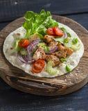 Очень вкусный зажаренный цыпленок и tortilla свежих овощей домодельный на деревенской разделочной доске Стоковая Фотография