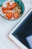 Очень вкусный здоровый завтрак и таблетка цифров на кухонном столе Стоковое фото RF
