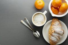 Очень вкусный кофе завтрака с круассаном и цитрусовыми фруктами - апельсинами Кофеин утра Француз, свежая выпечка и чашка кофе ил стоковое фото