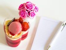 Очень вкусный красочный торт югурта с ручкой на тетради и розовых розах на белой таблице Стоковая Фотография