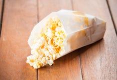 Очень вкусный попкорн в бумажном пакете на таблице Стоковая Фотография