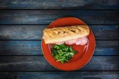 Очень вкусный сандвич с грибами ветчины и зеленым салатом на керамической плите Покрашенная деревянная предпосылка Взгляд сверху Стоковые Изображения