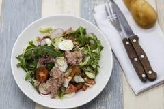 Очень вкусный салат свежего овоща с тунцом на белой плите фарфора с вилкой и ножом Стоковые Фотографии RF