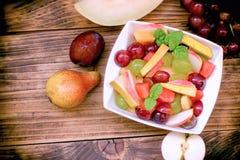 Очень вкусный фруктовый салат, вегетарианская еда в шаре на деревенской таблице Стоковое фото RF